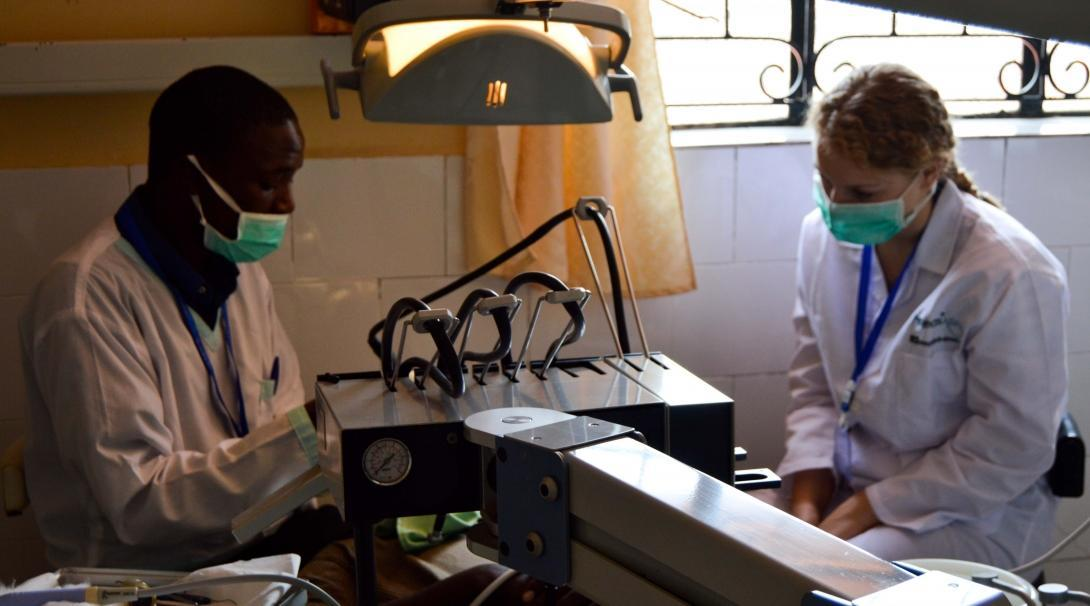 A dentist performs a dental procedure for a patient in Kenya as a student doing a Dentistry internship abroad observes.
